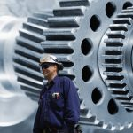 workers, mechanis with giant gear and cogwheels machinery in background